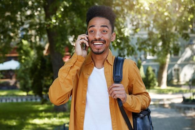 Portret van een jonge donkere gelukkig verbaasde man in een geel overhemd en een wit t-shirt met een rugzak op een schouder, wandelen in het park, praten aan de telefoon.
