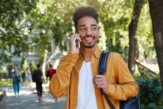 Portret van een jonge donkere lachende man draagt in een geel shirt en een wit t-shirt met een rugzak op een schouder, wandelen in het park en praten aan de telefoon, glimlachen en geniet van de dag.