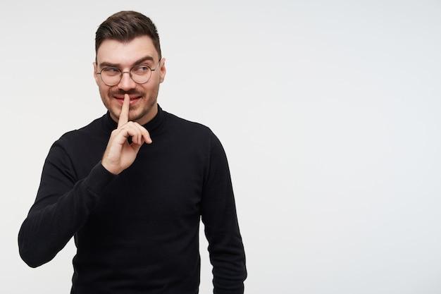 Portret van een jonge donkerharige man met kort kapsel die opgeheven wijsvinger op zijn mond houdt en sluw opzij kijkt, geïsoleerd op wit