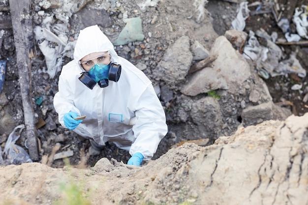 Portret van een jonge ecoloog in beschermend pak camera kijken tijdens het onderzoek van de rotsen
