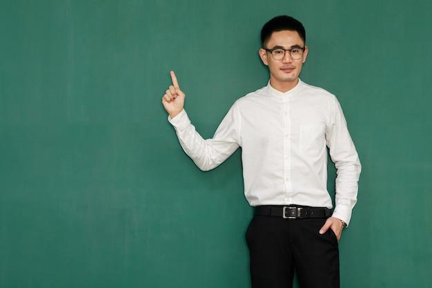 Portret van een jonge en knappe aziatische man met een bril en casual zakelijke kleding, een wit overhemd en een zwarte broek, poseert in gebaren van reclame en presenteert iets met zelfvertrouwen.