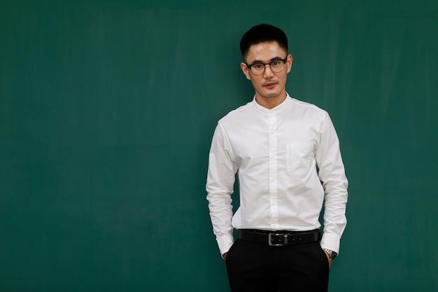 Portret van een jonge en knappe aziatische man met een bril en casual zakelijke kleding, wit overhemd en zwarte broek, staande pose met zelfvertrouwen met groene achtergrond en kopieerruimte.