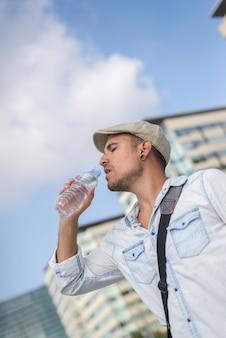Portret van een jonge en mannelijke man die buiten een water drinkt