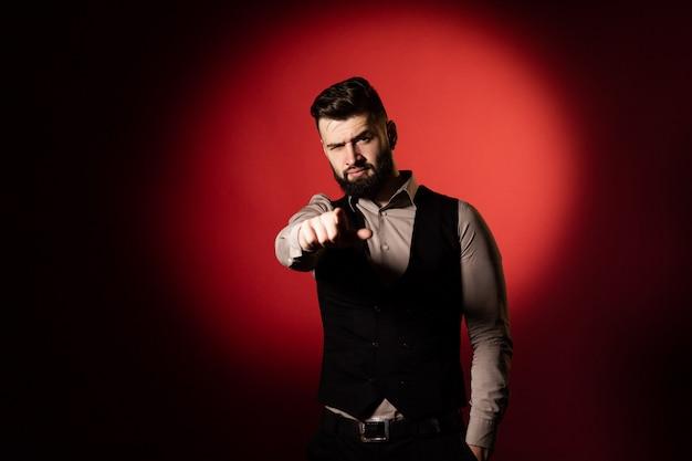 Portret van een jonge ernstige bebaarde man in een zwart vest op rode achtergrond. man wijzend op de camera