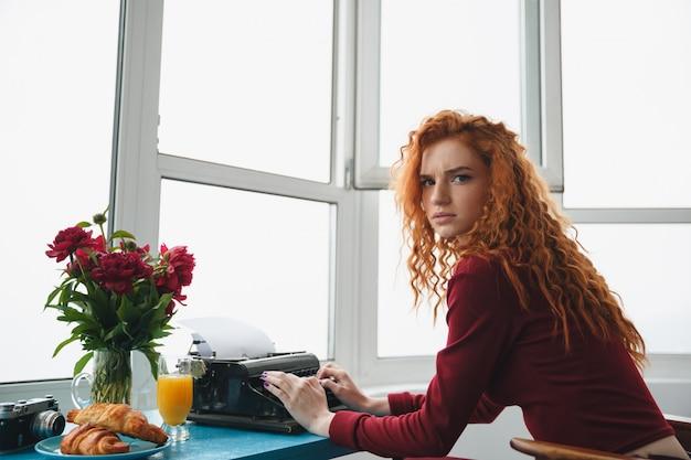 Portret van een jonge ernstige roodharige vrouw te typen