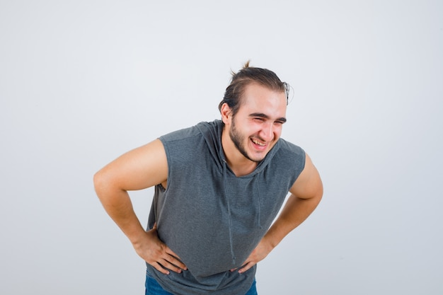 Portret van een jonge fit man poseren met de handen op de taille tijdens het buigen in mouwloze hoodie en op zoek vrolijk vooraanzicht