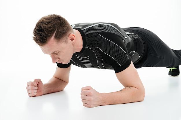 Portret van een jonge fitness man doet plank oefening