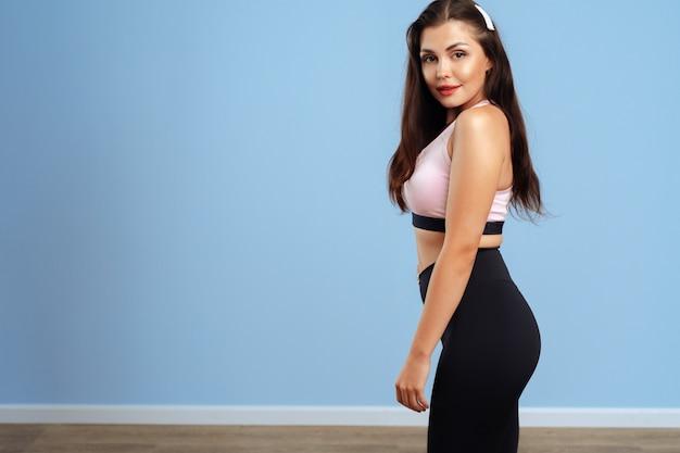 Portret van een jonge fitness vrouw in sportkleding het stellen in studio