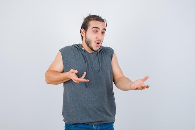 Portret van een jonge fitte man die iets toont terwijl hij opzij wijst in mouwloze hoodie en verwonderd vooraanzicht kijkt
