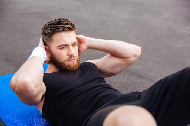 Portret van een jonge, geconcentreerde, knappe sportman die in de buitenlucht perstraining doet op een fitnessmat
