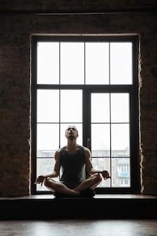 Portret van een jonge geconcentreerde sportman mediteren
