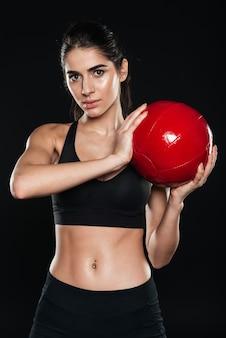 Portret van een jonge geconcentreerde sportvrouw die een fitnessbal vasthoudt en naar de voorkant kijkt over een zwarte muur
