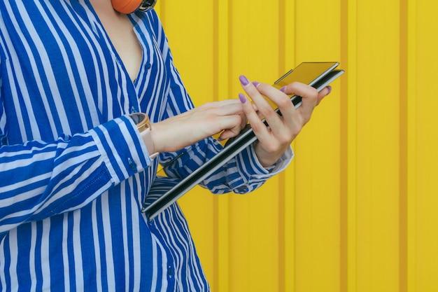 Portret van een jonge gekleurde laptop van de meisjesholding en wat betreft het scherm.
