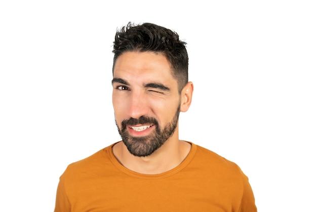 Portret van een jonge gelukkig man die lacht terwijl hij een oog knipoogt tegen witte ruimte