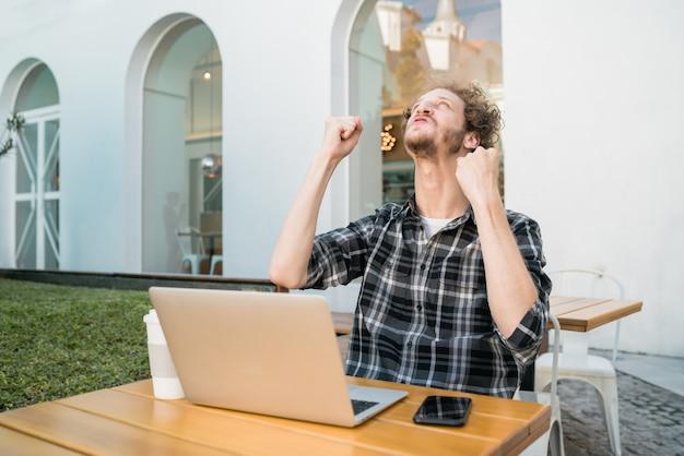 Portret van een jonge gelukkig man kijken naar laptop en goed nieuws vieren in een coffeeshop. succesvol concept.