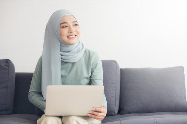 Portret van een jonge gelukkig moslimvrouw in hijab thuis werken met laptopcomputer zittend op de bank.