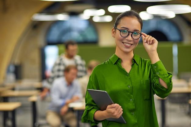 Portret van een jonge, gelukkige aziatische vrouw die haar bril aanpast met een digitale tablet en glimlacht naar