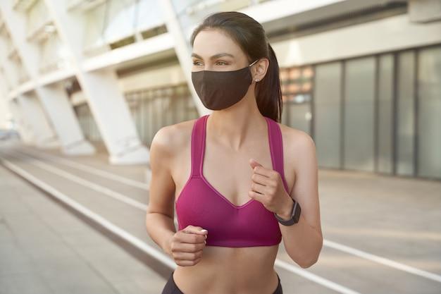 Portret van een jonge, gelukkige fitnessvrouw in korte kleding met een zwart beschermend gezichtsmasker