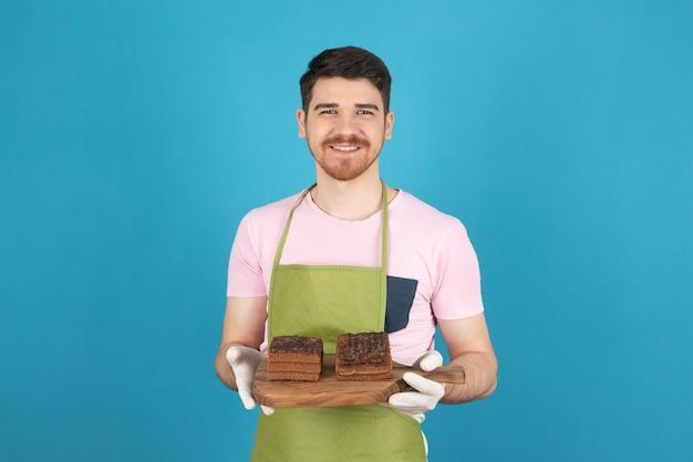 Portret van een jonge gelukkige man met plakjes chocoladetaart op een blauw.