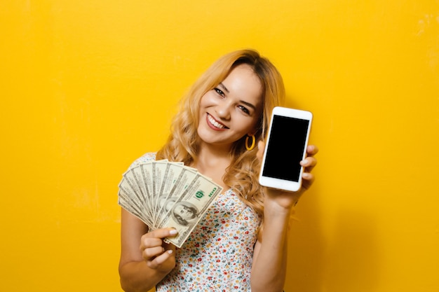Portret van een jonge gelukkige mooie de holdingstelefoon en bankbiljetten van het blondemeisje over gele achtergrond