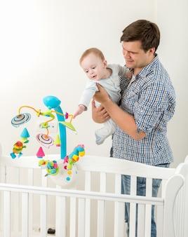 Portret van een jonge gelukkige vader die een nieuwe speelgoedcarrousel in een wieg toont aan zijn zoontje baby