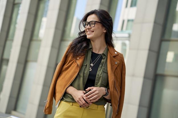 Portret van een jonge gelukkige vrouw die een smartphone vasthoudt die opzij kijkt en glimlacht terwijl ze verder loopt