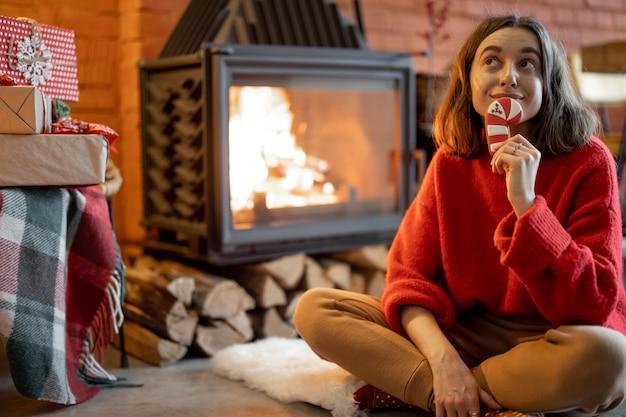 Portret van een jonge gelukkige vrouw met een kerstsnoep bij de open haard tijdens de wintervakantie