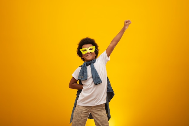 Portret van een jonge, gemengd rasjongen verkleed als een superheld. zwarte baby in superheld kostuum. de winnaar en het succes