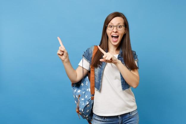 Portret van een jonge geschokte studente met een rugzak die een bril draagt en de wijsvinger opzij wijst op kopieerruimte geïsoleerd op een blauwe achtergrond. onderwijs in het concept van de middelbare schooluniversiteit.