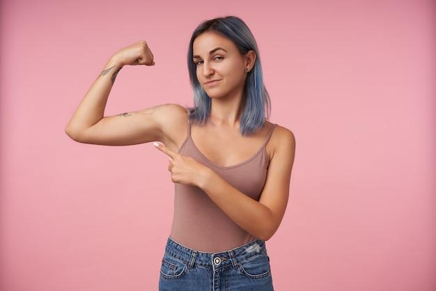 Portret van een jonge getatoeëerde vrouw met kort kapsel wijzend op haar opgeheven hand terwijl ze haar sterke biceps laat zien, staande op roze