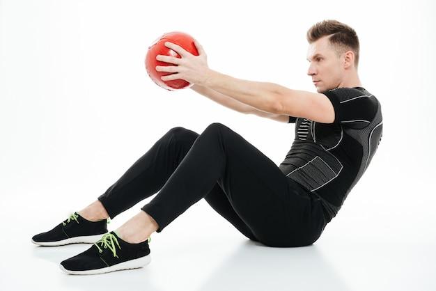 Portret van een jonge gezonde atletenmens die buikoefeningen doet