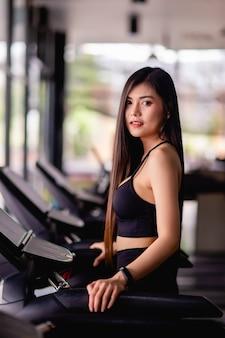 Portret van een jonge gezonde vrouw die op de loopband loopt, ze glimlacht tijdens de training in de sportschool, een gezond levensstijlconcept, kopieer de verticale afbeelding van de ruimte