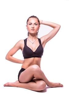 Portret van een jonge gezonde vrouw die yogaoefeningen doet, die over witte achtergrond wordt geïsoleerd