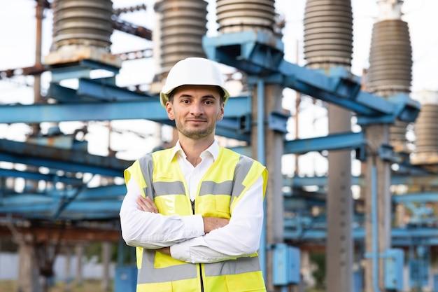 Portret van een jonge glimlachende aziatische elektrische arbeider met gevouwen armen op de krachtplaats portret van ingenieur