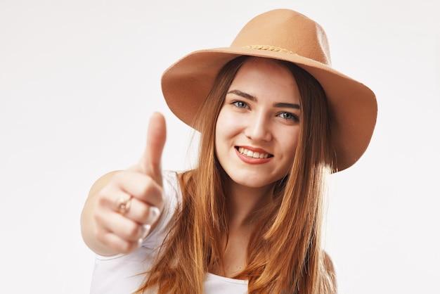 Portret van een jonge glimlachende blonde vrouw in beige hoed die de omhoog gehouden duim toont