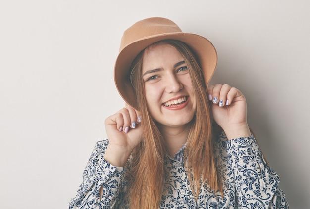 Portret van een jonge glimlachende blonde vrouw in beige hoed