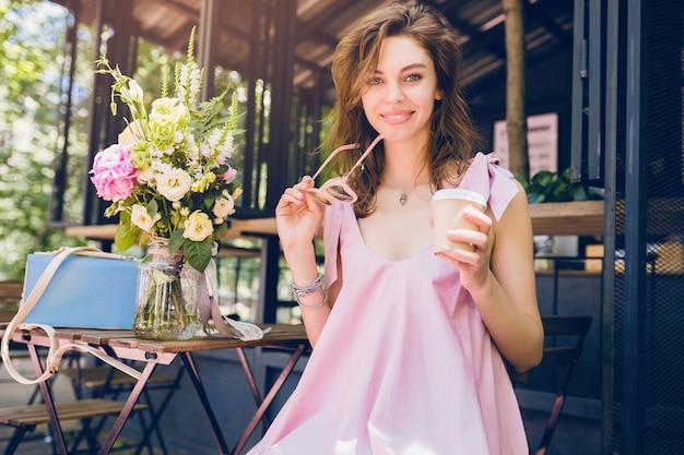 Portret van een jonge glimlachende gelukkige mooie vrouw die in café koffie drinkt