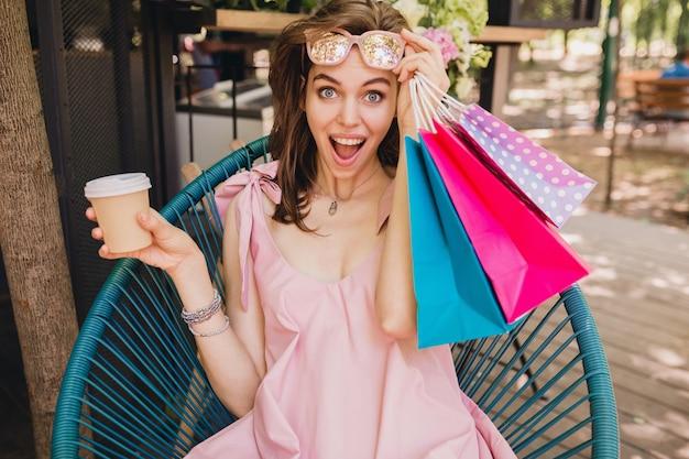 Portret van een jonge glimlachende gelukkige mooie vrouw met een opgewonden gezichtsuitdrukking die in een café zit met boodschappentassen die koffie drinkt