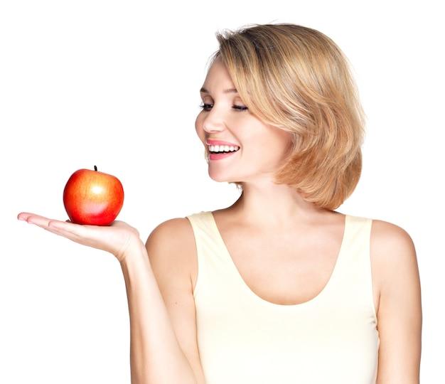 Portret van een jonge glimlachende gezonde vrouw met rode appel die op wit wordt geïsoleerd.