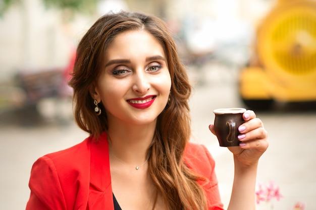 Portret van een jonge glimlachende kaukasische vrouw die de camerazitting met een kop van koffie in openlucht bekijkt