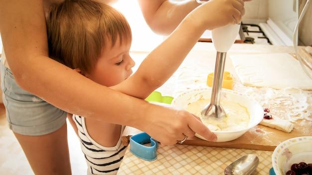 Portret van een jonge glimlachende moeder die haar 3 jaar oude peuterjongen leert bakken en koekjes maken in de keuken