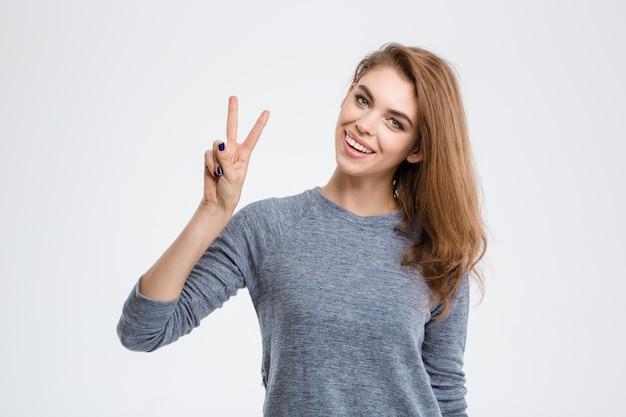 Portret van een jonge glimlachende vrouw die vredesteken toont dat op een witte achtergrond wordt geïsoleerd