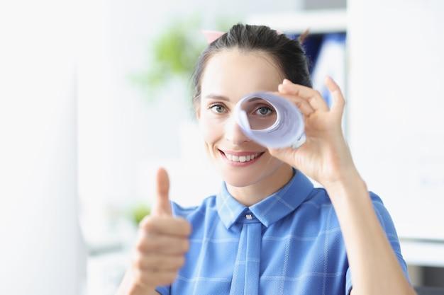 Portret van een jonge glimlachende vrouw houdt duimen omhoog en kijkt in een pijp gemaakt van papier, zoek naar