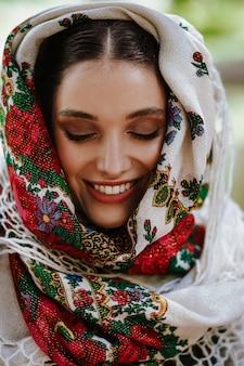 Portret van een jonge glimlachende vrouw in een traditionele geborduurde jurk
