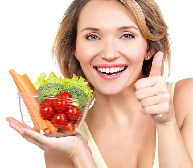 Portret van een jonge glimlachende vrouw met een plaat van groenten - die op wit wordt geïsoleerd.