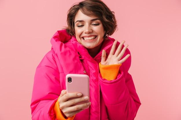 Portret van een jonge grappige vrouw in een warme jas die videogesprek voert en zwaait met de hand geïsoleerd op roze