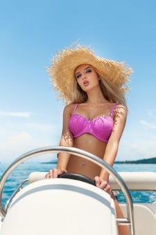 Portret van een jonge hete meid met lichte make-up in een roze bikini poseren terwijl je achter het stuur van een kleine motorboot. reizen. mariene schoonheid. golven. de zon. zee.