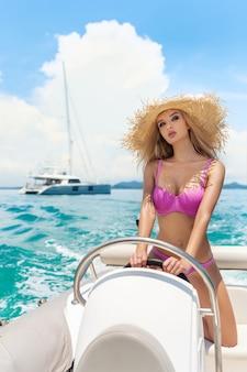 Portret van een jonge hete meid met lichte make-up in een roze bikini poseren terwijl je achter het stuur van een kleine motorboot, te midden van een rijk jacht. reizen. mariene schoonheid. de golven.