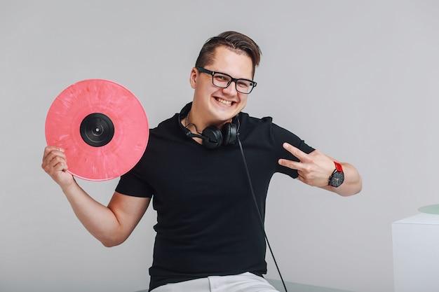 Portret van een jonge hipster met vinylplaten in handen, die een teken van overwinning tonen