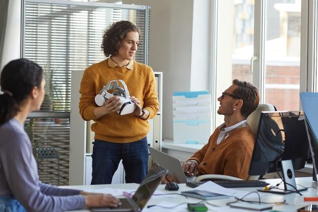 Portret van een jonge it-ontwikkelaar die een vr-headset vasthoudt terwijl hij samenwerkt met een team in de softwareproductiestudio, kopieer ruimte